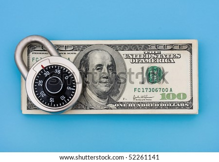 A stack of one hundred dollar bills with a combination lock on it sitting on a blue background, securing finances