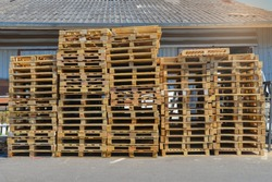 A stack of pallets sit outside a building.