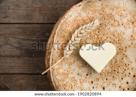 a stack of pancakes, a spike of wheat and a heart-shaped butter. wooden background. Pancake week. Russian, Ukrainian and Belarusian traditional food. space for text