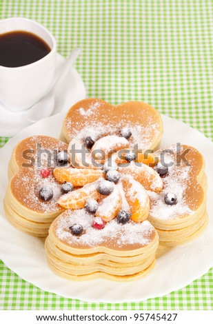 A stack of pancakes with berries and tangerine.