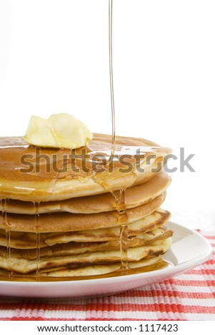 A stack of pancakes, with syrup drizzling down over the top. A dollop of butter sits on top. Country style.