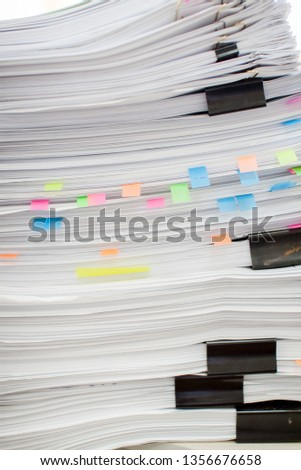 A stack of papers fastened with stationery clips and clips with stickers.
