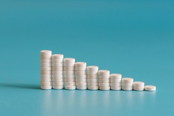 A stack of pills on a blue background. Growth graph made of stacked white pills - growing market and increasing demand for white pill and it's substitutes.