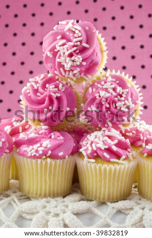 A stack of pink cupcakes for Breast Cancer Awareness Month, selective focus, vertical with copy space