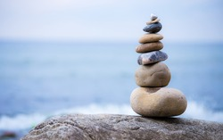A stack of round stones standing on the shore of a sea