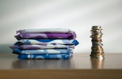 A stack of sanitary towels next to a taller stack of coins. Illustrating period poverty and unaffordability of sanitary materials for many women worldwide.