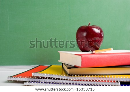 A stack of school books and an apple in front of a  blank chalkboard or blackboard background with copy space