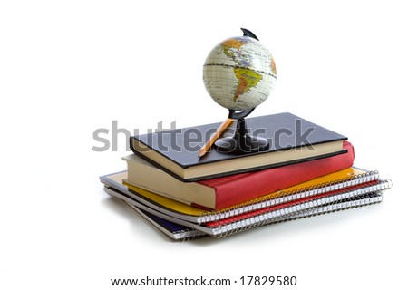 A stack of school books and notebooks with a miniature globe