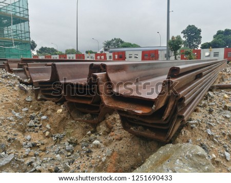 A stack of sheet piles. Sheet piles are sections of sheet materials with interlocking edges that are driven into the ground to provide earth retention and excavation support.