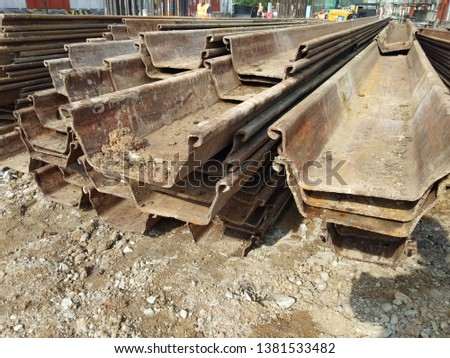 A stack of sheet piles. Sheet piles are sections of sheet materials with interlocking edges that are driven into the ground to provide earth retention and excavation support. #1381533482