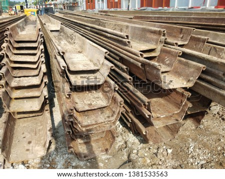 A stack of sheet piles. Sheet piles are sections of sheet materials with interlocking edges that are driven into the ground to provide earth retention and excavation support. #1381533563