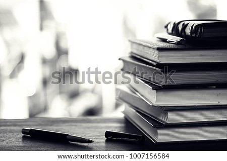 A stack of textbooks on the windowsill and writing utensils #1007156584