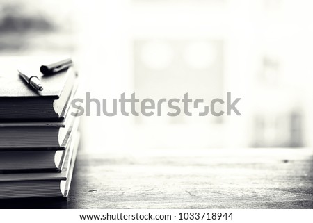 A stack of textbooks on the windowsill and writing utensils #1033718944