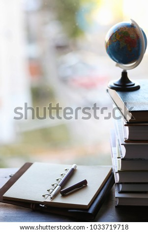 A stack of textbooks on the windowsill and writing utensils #1033719718