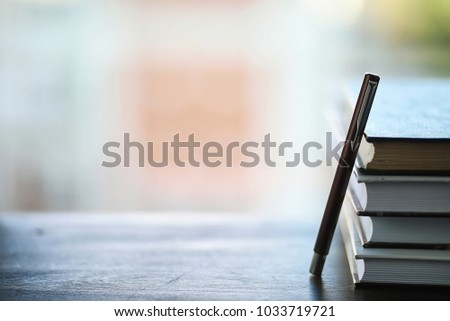 A stack of textbooks on the windowsill and writing utensils #1033719721
