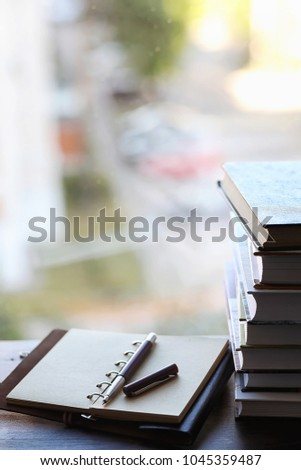 A stack of textbooks on the windowsill and writing utensils #1045359487