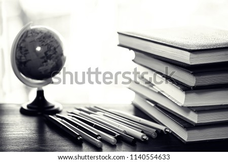 A stack of textbooks on the windowsill and writing utensils #1140554633