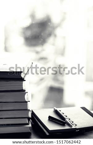 A stack of textbooks on the windowsill and writing utensils