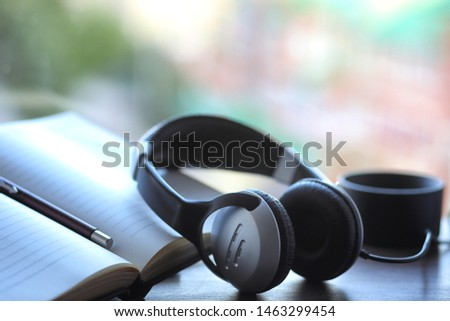 A stack of textbooks with black headphones on a table