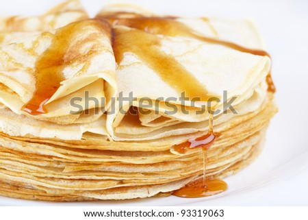 A stack of thin pancakes with honey
