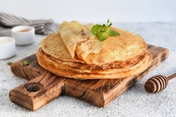 A stack of thin pancakes with sour cream and honey on a wooden board on a concrete background.