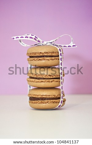 A stack of three chocolate macarons.