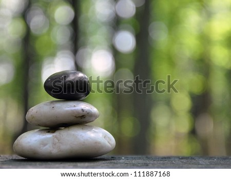 A stack of three zen rocks are in the forest with trees in the background to add a text message.