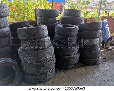 A stack of used tyres at auto shop, can be recycled as decorations and crafts.