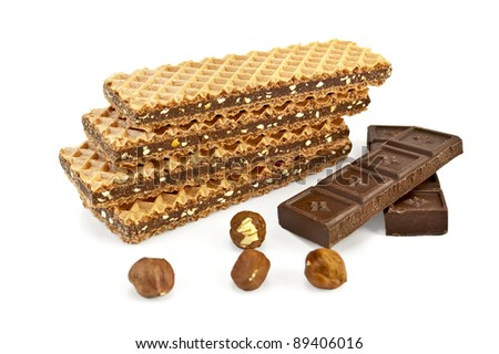 A stack of waffles, interlayered with chocolate, two bars of chocolate and four nuts isolated on white background