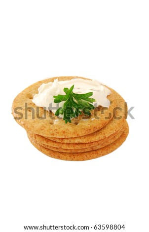 A stack of whole wheat crackers on white with cream cheese and parsley