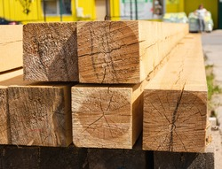 a stack of wooden balks, wooden balks, beams at a sawmill, a warehouse of beams on the site of a building materials store. Wood, timber, wood beams, construction material