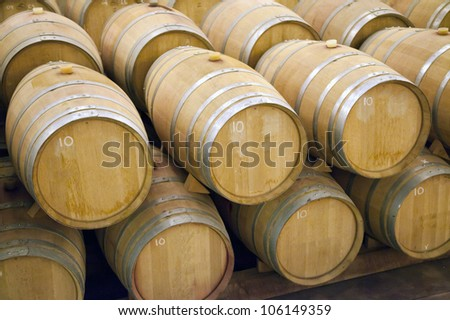 A stack of wooden barrels in a winery, aging wine.