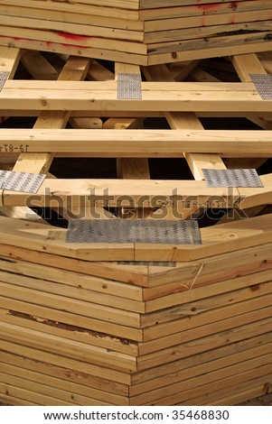 A stack of wooden roof trusses to frame a new house being built, as delivered to the construction site.