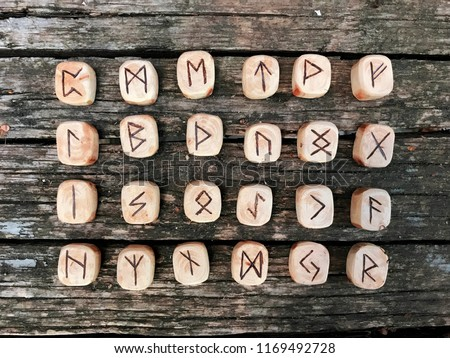 A stack of wooden runes at forest. Wooden runes lie on a old wood background. Runes are cut from wooden blocks. On each rune symbol for fortune telling is designated.