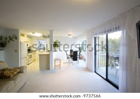 A staged dining room, kitchen, and living room in a condominium.