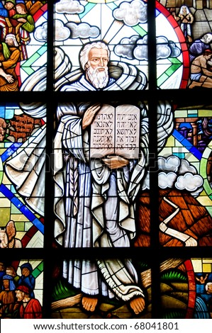 A stained glass window of of Moses holding the Ten Commandment Tables. - stock photo
