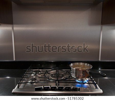 A stainless steel pan full of boiling water on a gas hob in a modern kitchen.