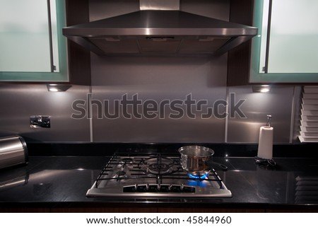 A stainless steel pan on a gas hob in a modern kitchen.