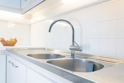 A stainless steel sink in the kitchen with white tiles on the wall