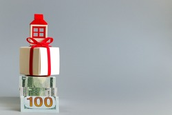 A staircase made of a hundred-dollar bill leads to a box tied with a red ribbon and a figure representing a house. The concept of saving and buying your dream home. Free space