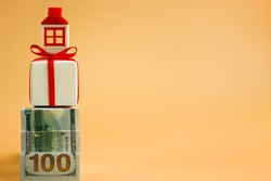 A staircase made of a hundred-dollar bill leads to a box tied with a red ribbon and a figure representing a house. Mortgage concept of real estate. Free space for text.
