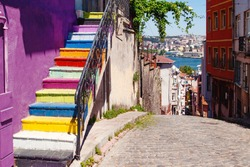 A staircase painted with bright colors on the side of a purple wall in Balat district of Istanbul with an open view of the Golden Horn.