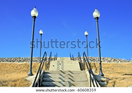 A stairway leading up to an unknown location with light poles on both sides.