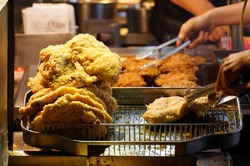 A stall vendor frying in boiling oil the crispy deep-fried chicken cutlets, one of local people's favorite street-foods, in Shilin Night Market, Taipei, where many traditional snacks can be savored