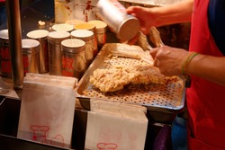 A stall vendor seasoning with pepper and salt the crispy deep-fried chicken cutlets, one of local people's favorite street-foods, in Raohe Night Market, Taipei, where many yummy snacks can be savored