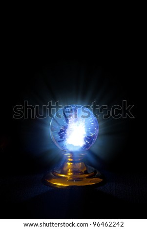 A stand alone crystal ball, glowing with rays shooting forth and strange patterns within.