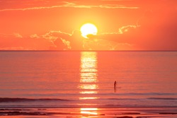 A stand up paddle boarder glides past a vibrant orange sunset at Cable Beach in Broome, Western Australia