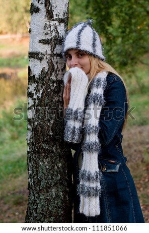 A standing girl in a cup and scarf and jeans coat in a forest