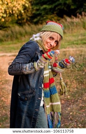 A standing girl in a cup and scarf and mittens and jeans coat in a forest