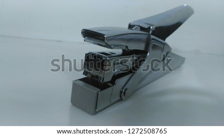 A stapler is a mechanical device that joins pages of paper or similar material by driving a thin metal staple through the sheets and folding the ends. Staplers are widely used in government, business,